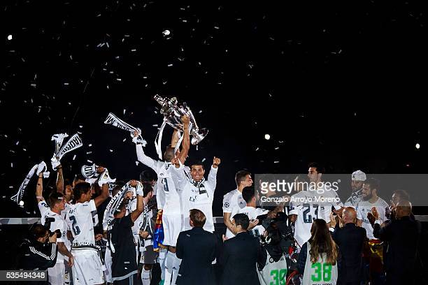 Pepe of Real Madrid CF stand the trophy behind his teammate aCristiano Ronaldo as they celebrate with their fans at Santiago Bernabeu Stadium the day...