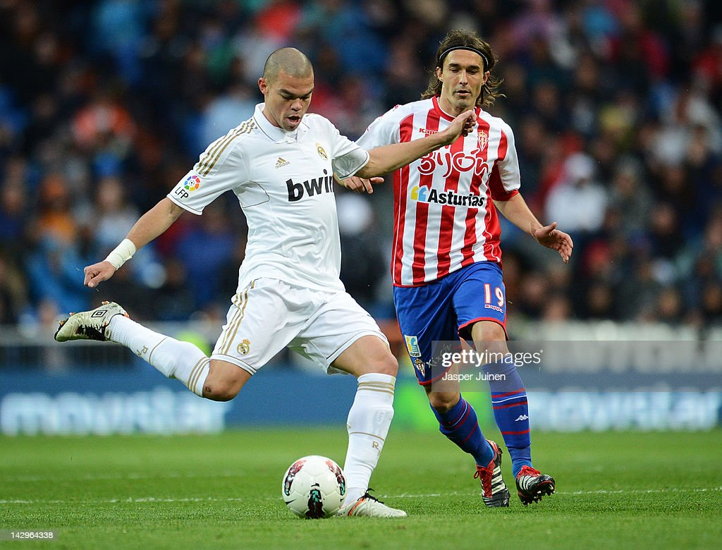 Pepe (L) of Real Madrid duels for the ball with Gaston Sangoy of Real Sporting de Gijon during the La Liga match between Real Madrid CF and Real Sporting de Gijon at the Estadio Santiago Bernabeu on April 14, 2012 in Madrid, Spain.
