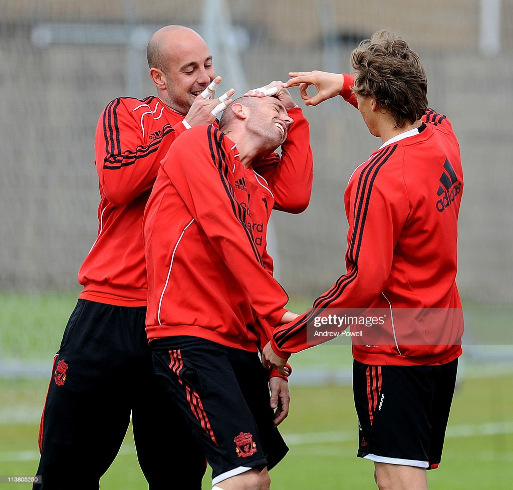 Pepe Reina (L) and Lucas Leiva (R) of Liverpool flick team mate Raul Meireles' ear during a Liverpool training session at Melwood Training Ground on May 6, 2011 in Liverpool, England.