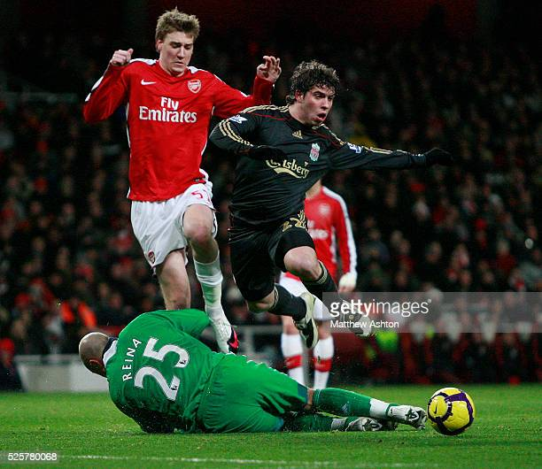 Pepe Reina in action with Emiliano Insua of Liverpool and Nicklas Bendtner of Arsenal
