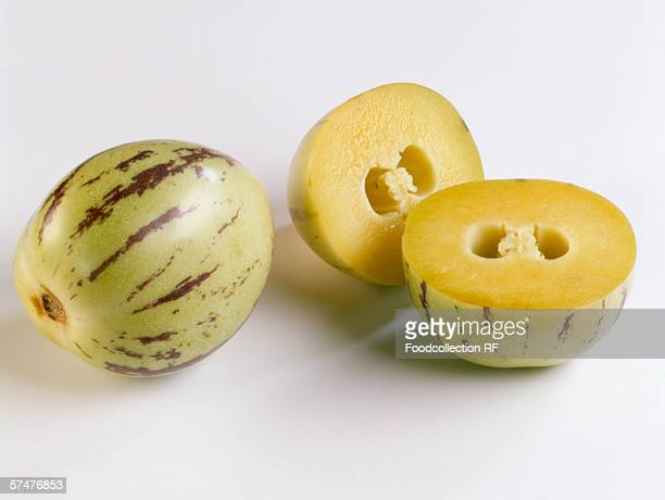 a pepino melon beside two pepino melon halves - pepino stock pictures, royalty-free photos & images