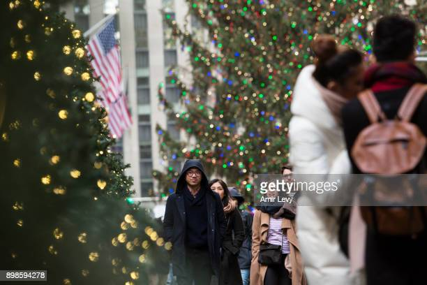 Pepole walk by Christmas decorated trees along Rockefeller Center on Christmas day on December 25 2017 in New York City Security in New York is on...