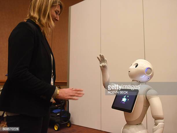 Pepper a humanoid robot by Aldebaran Robotics and SoftBank Mobile interacts with Aurore Chiquot in the media room during CES Press Day January 5 2016...