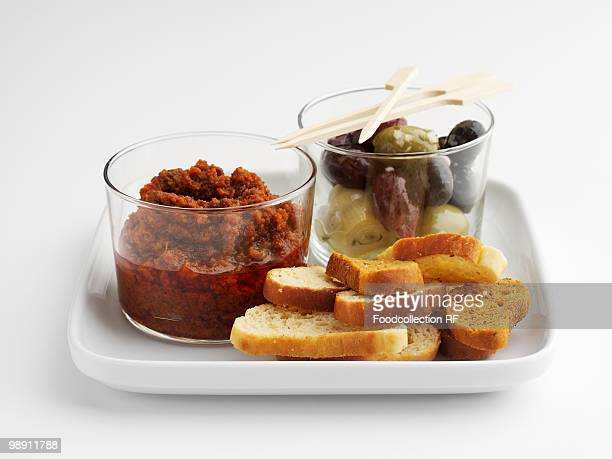 pepper and tomato tapenade, olives and slices of bread, close-up - olive pimento stock photos and pictures