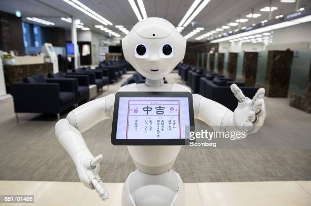 A Pepper humanoid robot developed by SoftBank Group Corp stands at the Mizuho Bank Ltd branch inside the Mizuho Financial Group Inc headquarters in...