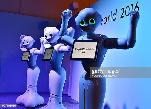 'Pepper' humanoid robots from Japan's telecommunication giant Softbank dance to attract customers at the 'Pepper World' exhibition to promote show...