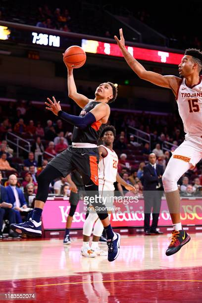 Pepperdine Waves guard Colbey Ross scores over USC Trojans forward Isaiah Mobley during a college basketball game between the Pepperdine Waves and...