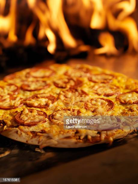 pepperoni pizza in a wood burning oven - pepperoni pizza stock photos and pictures