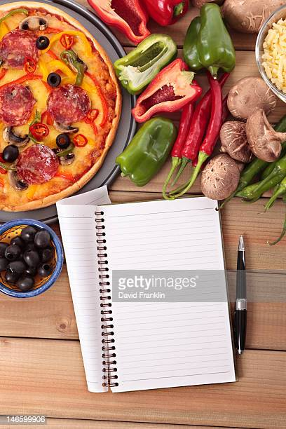 A pepperoni pizza, ingredients and a notebook