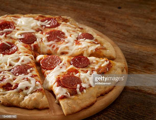 pepperoni pizza on a wood background - pepperoni pizza stock photos and pictures