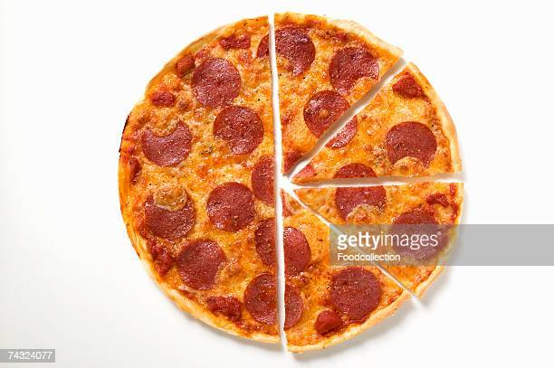 pepperoni pizza, one half cut into slices - pepperoni pizza stock photos and pictures