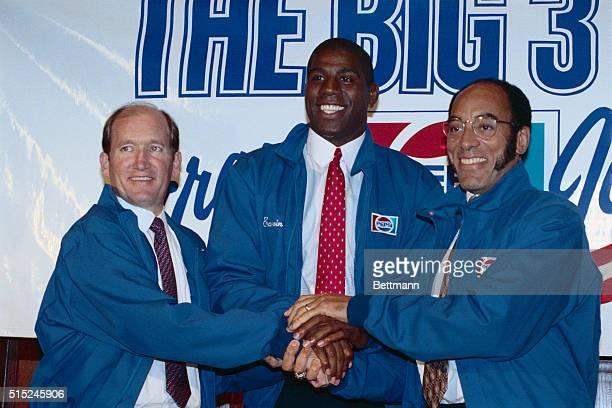 PepsiCola President Criag E Weatherup Earvin Magic Johnson of the NBA Los Angeles Lakers and Black Enterprise magazine editor Earl G Graves clasp...