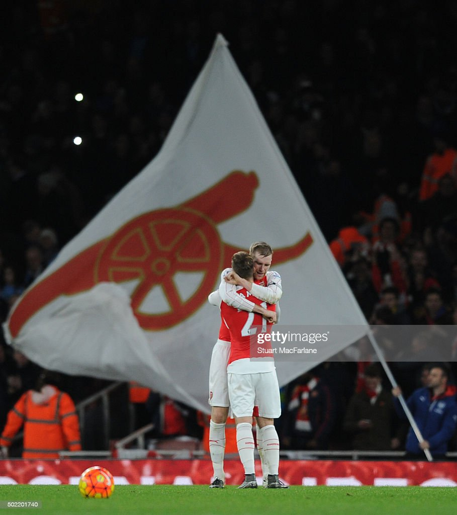 Per Mertesacker and Aaron Ramsey celebrate the Arsenal win after the Barclays Premier League match between Arsenal and Manchester City at Emirates Stadium on December 21, 2015 in London.