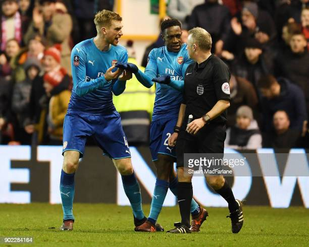 Per Mertesacker and Danny Welbeck complain to referee John Moss after the 2nd Nottingham Forest penalty during the FA Cup 3rd Round match between...