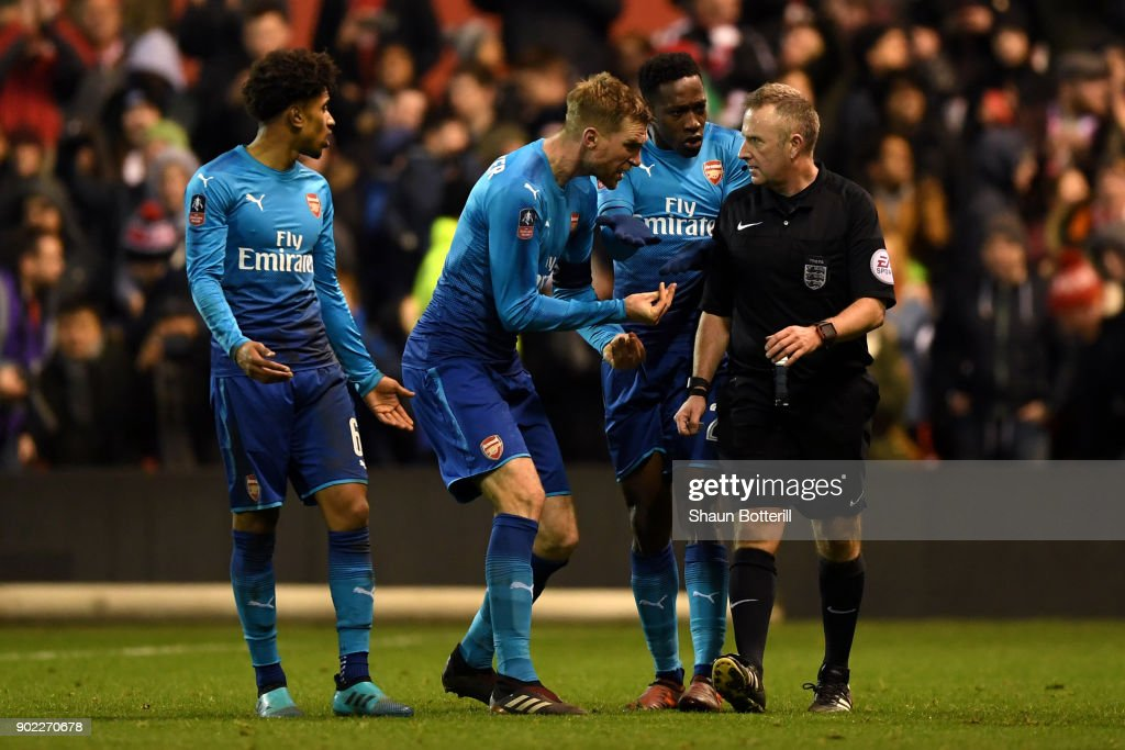 Per Mertesacker (2ndL) and Danny Welbeck (2ndR) of Arsenal react with referee Jonathan Moss after he awarded Nottingham Forest's fourth goal during The Emirates FA Cup Third Round match between Nottingham Forest and Arsenal at City Ground on January 7, 2018 in Nottingham, England.