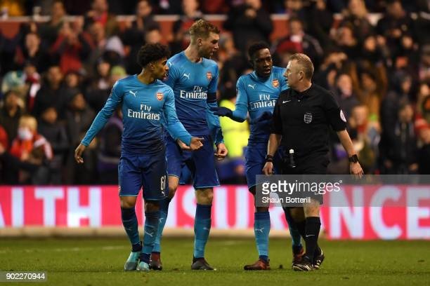 Per Mertesacker and Danny Welbeck of Arsenal react with referee Jonathan Moss after he awarded Nottingham Forest's fourth goal during The Emirates FA...