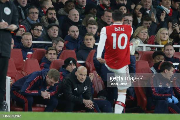 Per Mertesacker and Fredrik Ljungberg of Arsenal look on as Mesut Ozil kicks his gloves in the air in frustration after he is subbed during the...