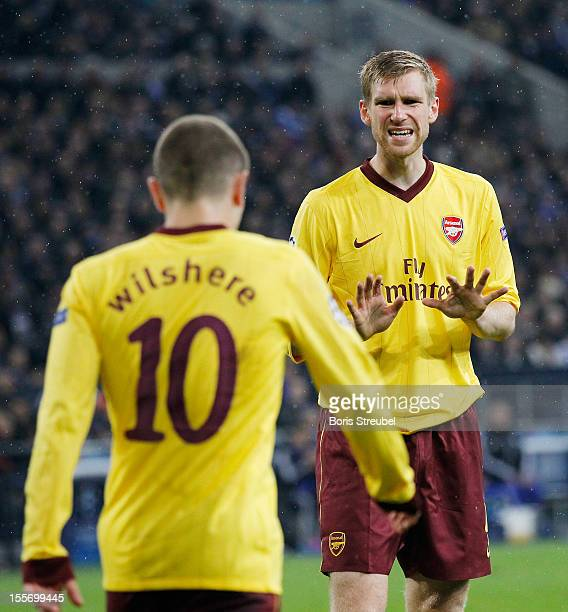 Per Mertesacker and Jack Wilshere of Arsenal react during the UEFA Champions League group B match between FC Schalke 04 and Arsenal FC at...