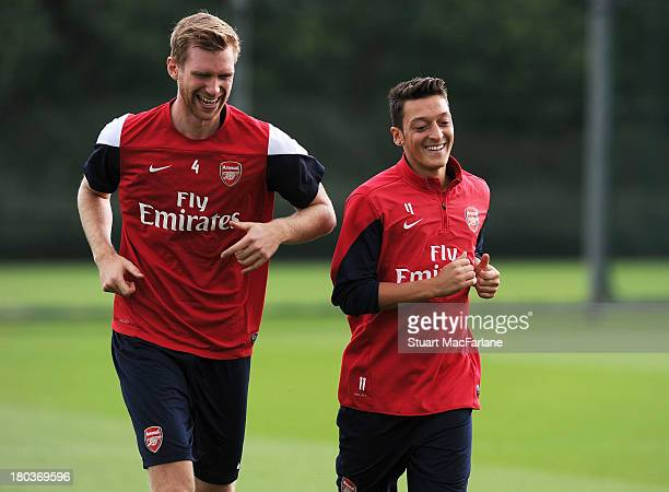 Per Mertesacker and Mesut Oezil of Arsenal during a training session at London Colney on September 12, 2013 in St Albans, England.