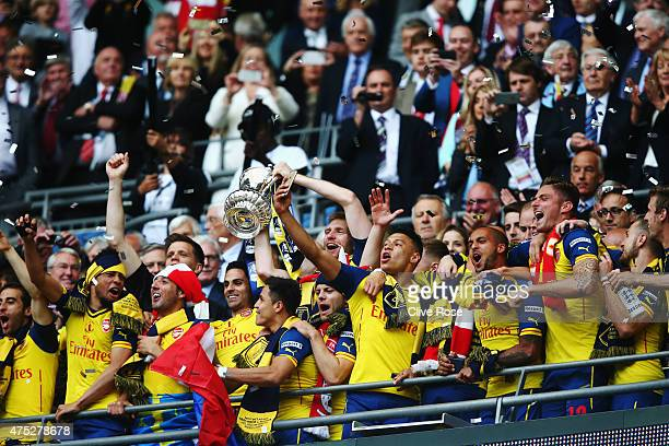Per Mertesacker and Mikel Arteta of Arsenal lift the trophy in celebration after the FA Cup Final between Aston Villa and Arsenal at Wembley Stadium...