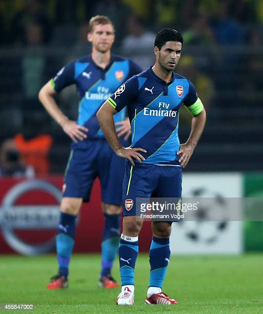 Per Mertesacker and Mikel Arteta of Arsenal looks dejected during the UEFA Champions League Group D match between Borussia Dortmund and Arsenal at...