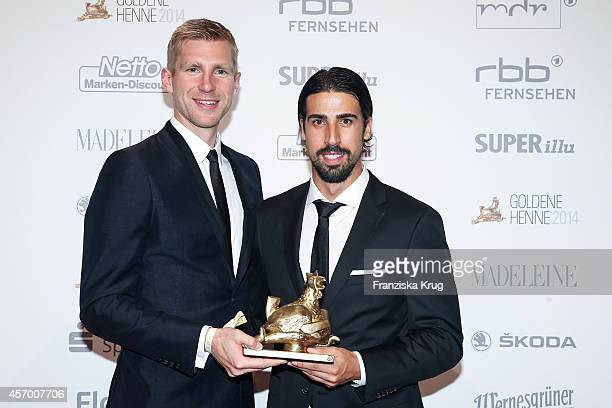 Per Mertesacker and Sami Khedira attend Madeleine at Goldene Henne 2014 on October 10 2014 in Leipzig Germany