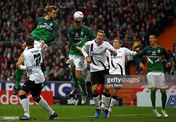 Per Mertesacker and Sebastian Proedl of Bremen go up for a header with Maik Franz of Frankfurt during the Bundesliga match between SV Werder Bremen...