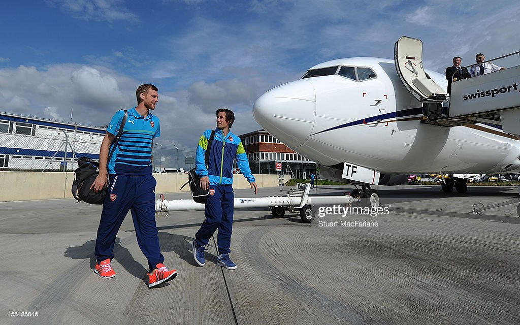 Per Mertesacker and Tomas Rosicky of Arsenal board the team flight at Luton Airport on September 15, 2014 in St Albans, England. Photo by Stuart MacFarlane/Arsenal FC via Getty Images)