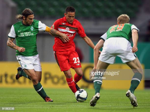 Per Mertesacker and Torsten Frings of Bremen as well as Deniz Naki of St. Pauli battle for the ball during the DFB Cup second round match between SV...