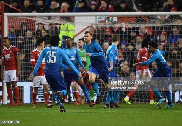 Per Mertesacker celebrates scoring the 1st Arsenal goal during the FA Cup 3rd Round match between Nottingham Forest and Arsenal at City Ground on...