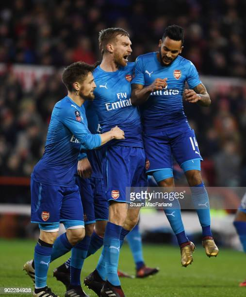 Per Mertesacker celebrates scoring the 1st Arsenal goal with Mathieu Debuchy and Theo Walcott during the FA Cup 3rd Round match between Nottingham...