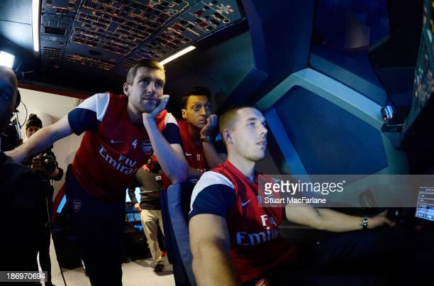 Per Mertesacker Mesut Oezil and Lukas Podolski in the Emirates' A380 flight simulator on October 31 2013 in Greenwich England