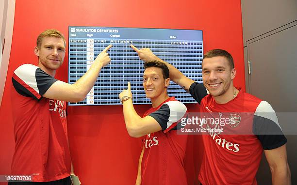 Per Mertesacker Mesut Oezil and Lukas Podolski of Arsenal at the Emirates Aviation Experience on October 31 2013 in Greenwich England