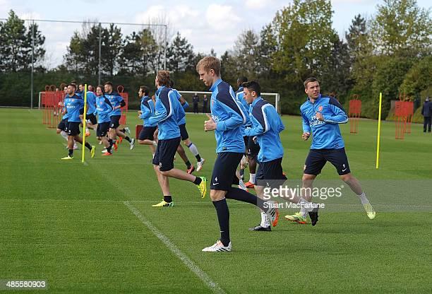 Per Mertesacker, Mesut Ozil and Lukas Podolski of Arsenal during a training session at London Colney on April 19, 2014 in St Albans, England.
