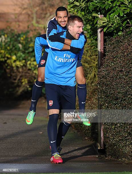 Per Mertesacker of Arsenal carries Theo Walcott on his back before a training session at London Colney on January 3, 2014 in St Albans, England.