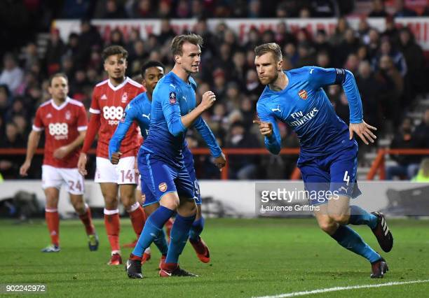 Per Mertesacker of Arsenal celebrates scoring the first Arsenal goal with Rob Holding during The Emirates FA Cup Third Round match between Nottingham...