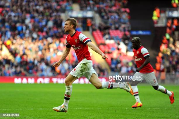 Per Mertesacker of Arsenal celebrates scoring the first goal during the FA Cup Semi-Final match between Wigan Athletic and Arsenal at Wembley Stadium...