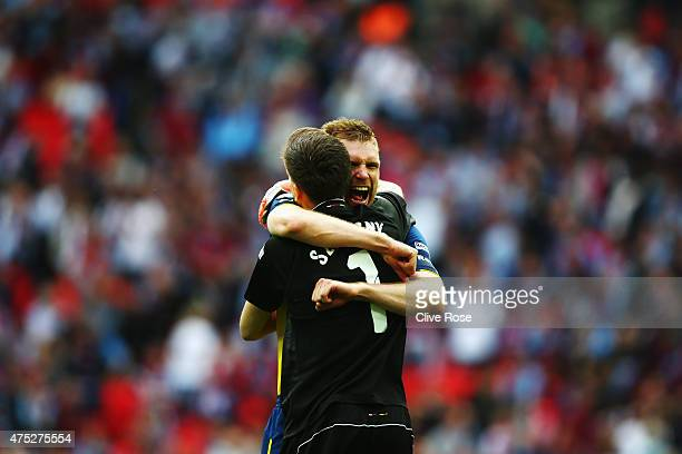 Per Mertesacker of Arsenal celebrates victory with Wojciech Szczesny after the FA Cup Final between Aston Villa and Arsenal at Wembley Stadium on May...