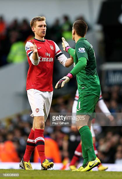 Per Mertesacker of Arsenal celebrates with his goalkeeper Wojciech Szczesny after scoring his team's first goal during the Barclays Premier League...