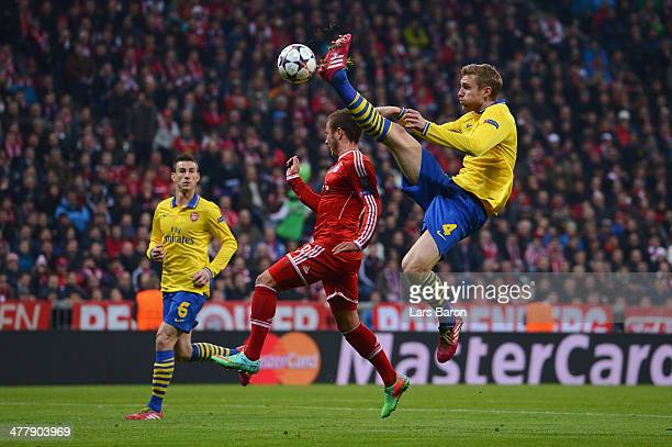 Per Mertesacker of Arsenal challenges for the ball with Mario Goetze of Bayern Muenchen during the UEFA Champions League round of 16 second leg match...