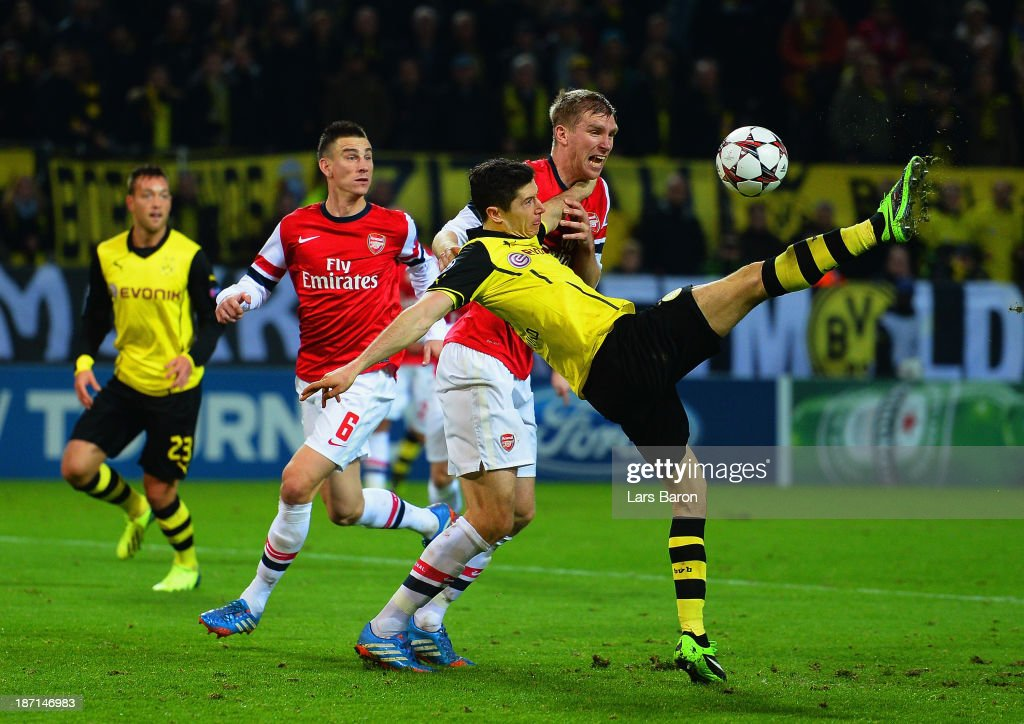 Per Mertesacker of Arsenal challenges Robert Lewandowski of Borussia Dortmund during the UEFA Champions League Group F match between Borussia Dortmund and Arsenal at Signal Iduna Park on November 6, 2013 in Dortmund, Germany.