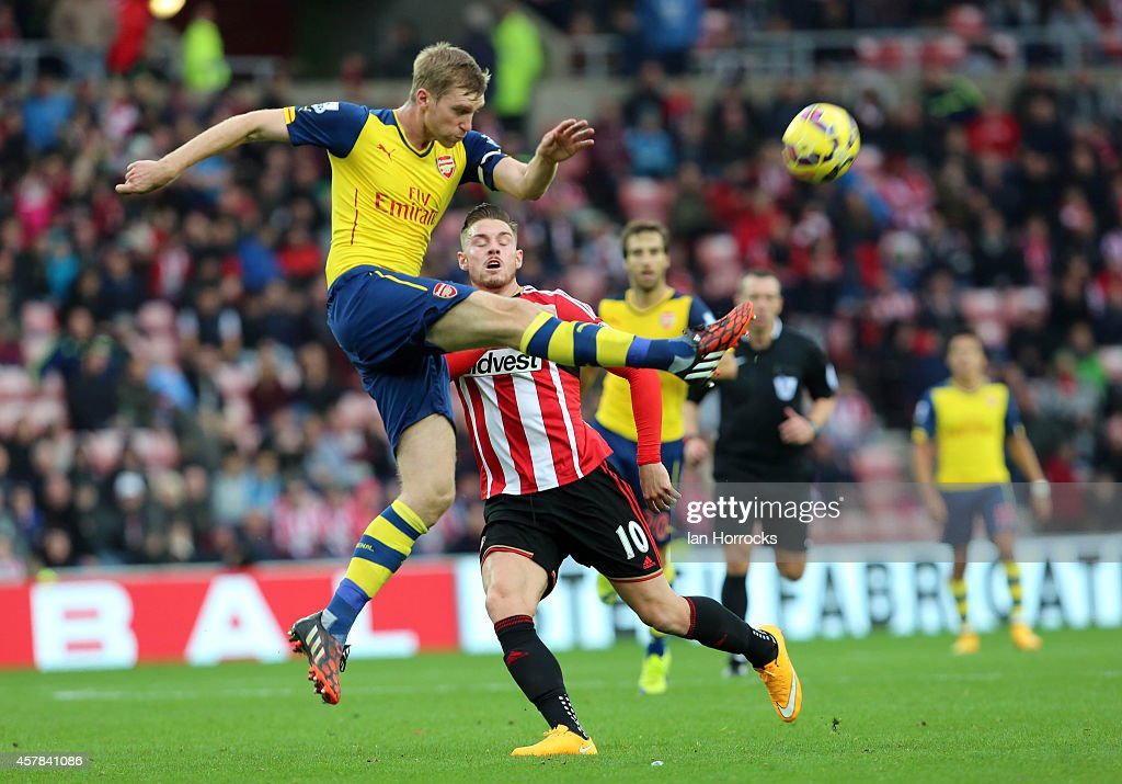 Per Mertesacker of Arsenal (L) clears the ball against Connor Wickham of Sunderland (R) during the Barclays Premier League match between Sunderland AFC and Arsenal FC at The Stadium of Light on October 25, 2014 in Sunderland, England.