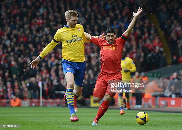 Per Mertesacker of Arsenal competes with Luis Suarez of Liverpool during the Barclays Premier League match between Liverpool and Arsenal at Anfield...