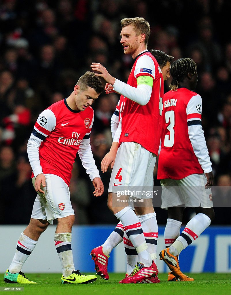 Per Mertesacker of Arsenal congratulates Jack Wilshere of Arsenal on scoring his second goal during the UEFA Champions League Group F match between Arsenal and Olympique de Marseille at Emirates Stadium on November 26, 2013 in London, England.