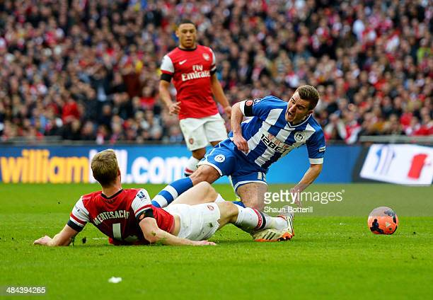 Per Mertesacker of Arsenal fouls Callum McManaman of Wigan Athletic in the penalty area during the FA Cup SemiFinal match between Wigan Athletic and...