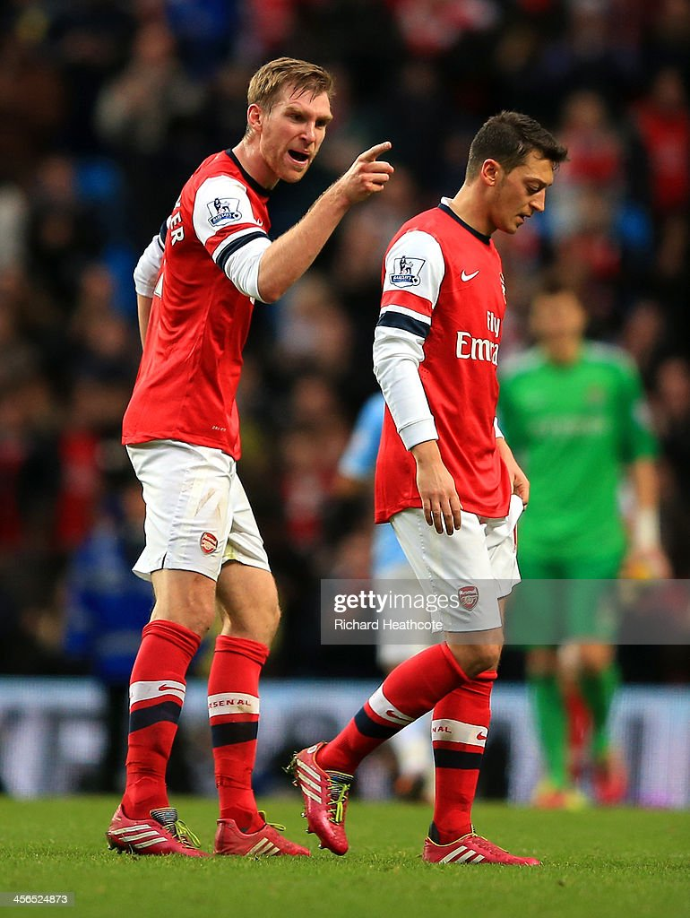 Per Mertesacker of Arsenal has words with Mesut Oezil of Arsenal during the Barclays Premier League match between Manchester City and Arsenal at Etihad Stadium on December 14, 2013 in Manchester, England.