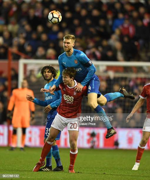 Per Mertesacker of Arsenal heads the ball away under pressure from Kieran Dowell of Forest during the Emirates FA Cup 3rd Round match between...