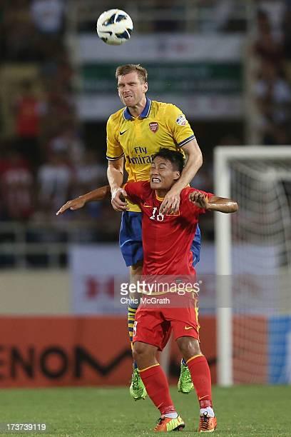Per Mertesacker of Arsenal heads the ball over the top of Mac Hong Quan of Vietnam during the international friendly match between Vietnam and...