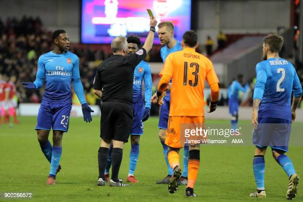 Per Mertesacker of Arsenal is booked for protesting during The Emirates FA Cup Third Round between Nottingham Forest and Arsenal at City Ground on...