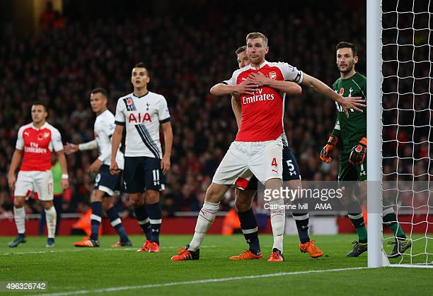 Per Mertesacker of Arsenal is held back by Jan Vertonghen of Tottenham Hotspur as they wait for a corner during the Barclays Premier League match...